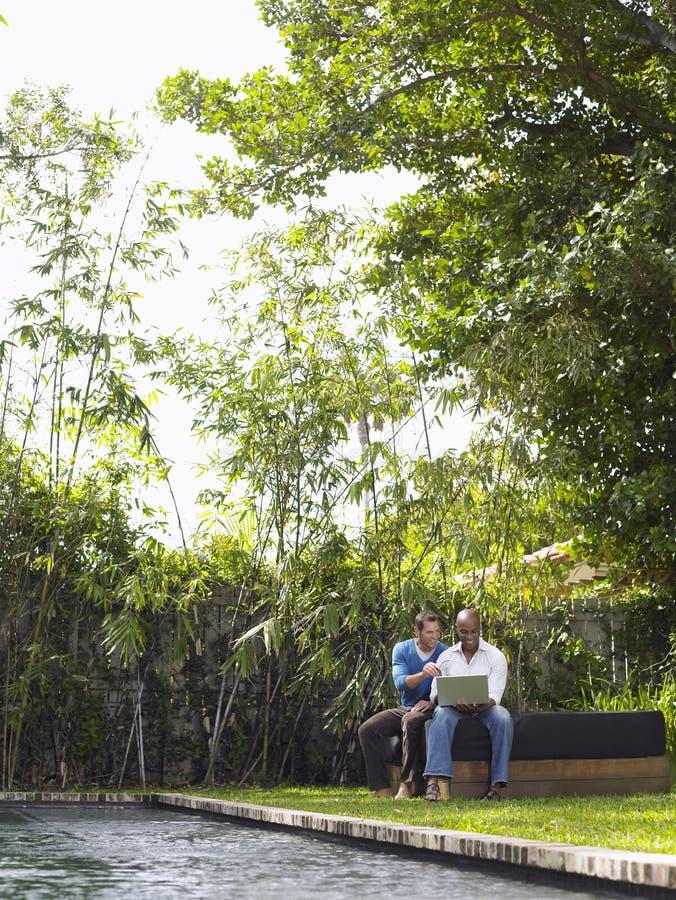 Многонациональные люди используя компьтер-книжку в саде стоковая фотография rf