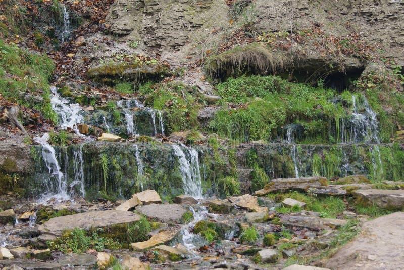Многоуровневый каскад чистого холодного прозрачного потока горы на горных склонах стоковое фото
