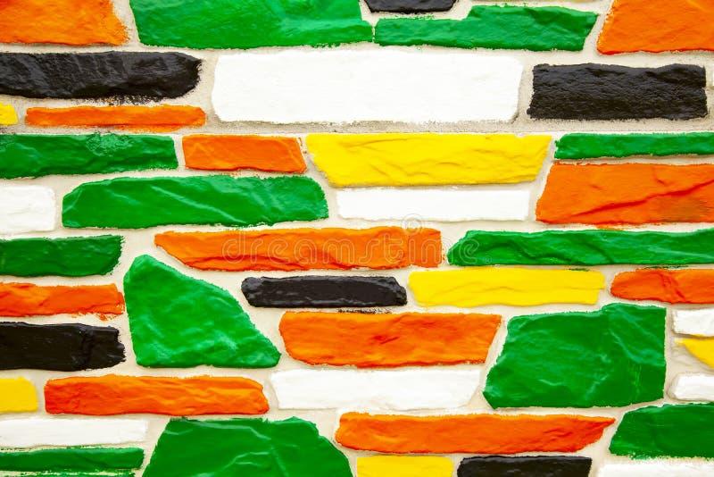 Многоцветная кирпичная стена в зеленом и желтом и оранжевом цветах стоковые фотографии rf