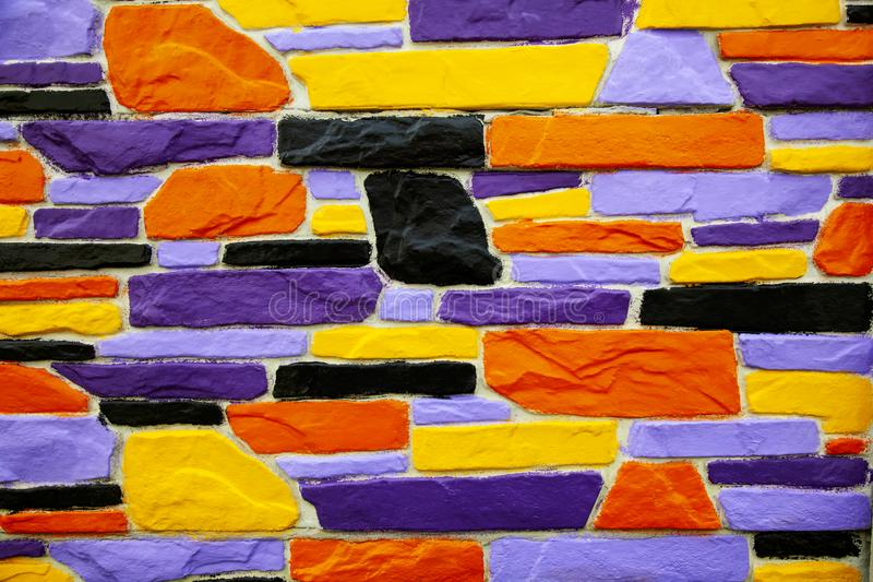 Многоцветная фиолетовая и оранжевая кирпичная стена стоковая фотография rf