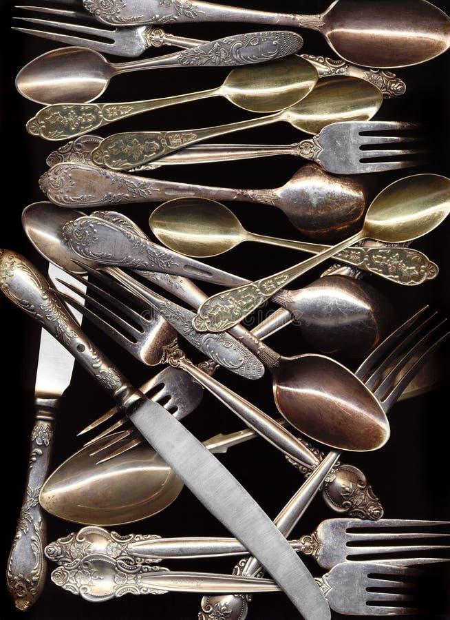 Много античных ложек, ножи, вилки на черной предпосылке стоковые изображения rf