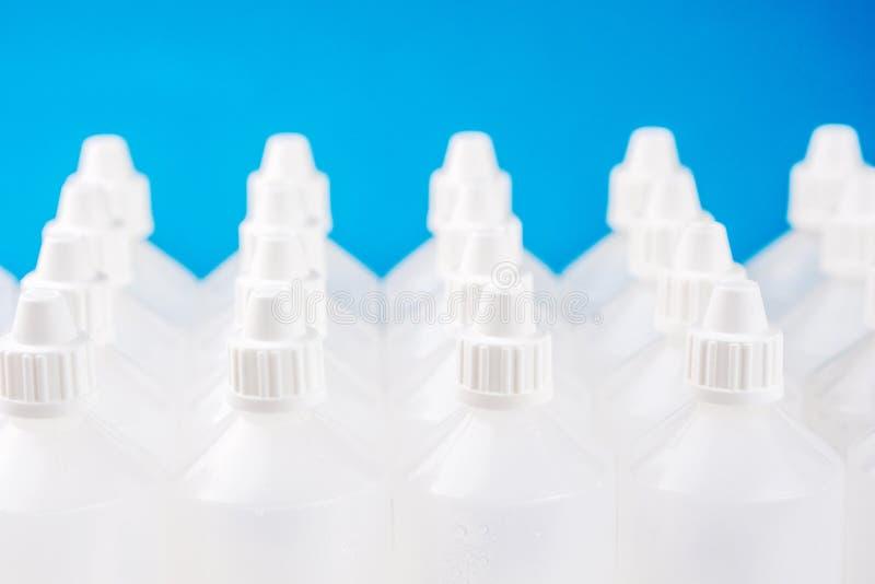 Много белых просвечивающих бутылок на сини запачкали предпосылку стоковая фотография rf