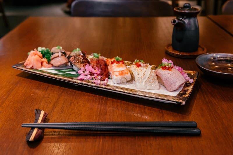 Много видов японских суш на керамической плите на деревянной таблице в r стоковые фотографии rf