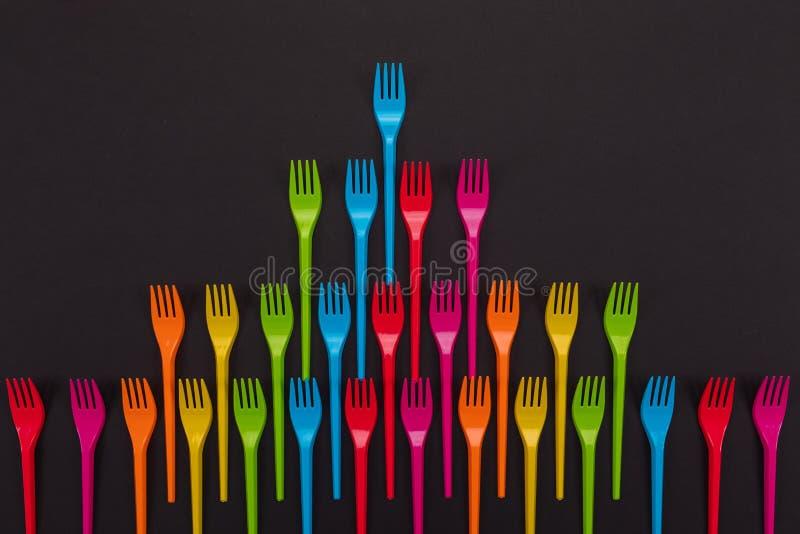 Много вилок цвета пластиковых на яркой предпосылке стоковые фото