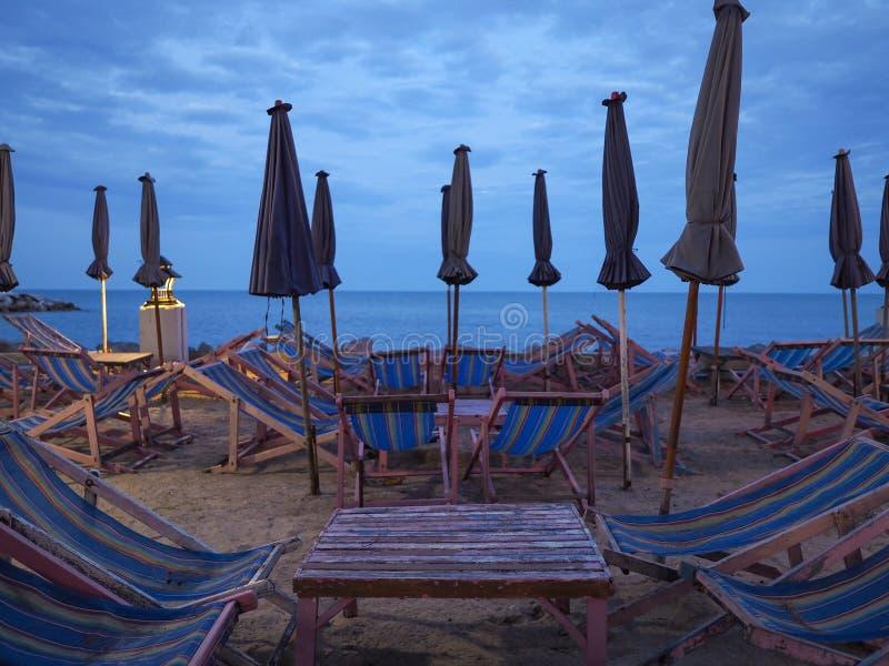Много деревянных deckchairs и зонтиков на песке на пляже захода солнца стоковое изображение rf