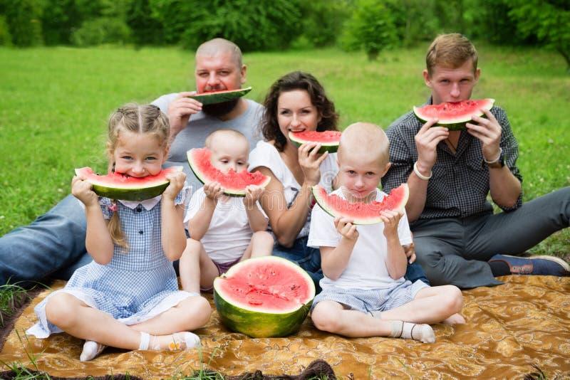 Многодетная семья есть арбуз стоковые изображения