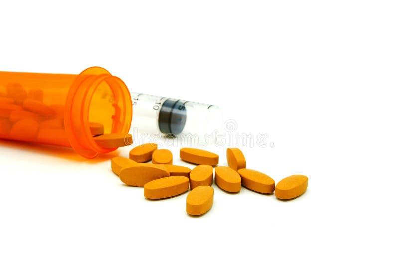 Много желтых пилюлек из оранжевой бутылки медицины и запачканной пластичной впрыски при космос экземпляра изолированный на белой  стоковое фото rf