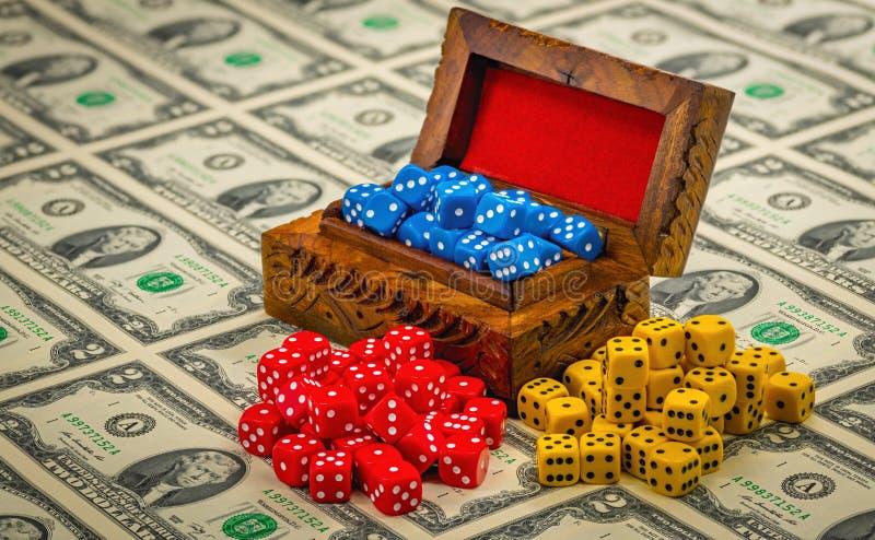 Много играя кости в деревянной коробке и на деньгах стоковые фото