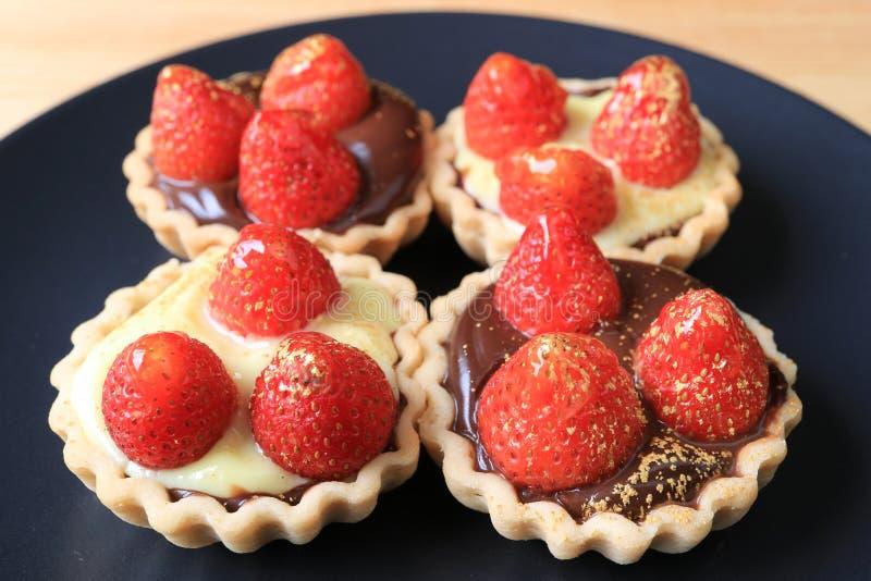 Много из мини пирогов шоколада покрыли с свежими клубниками и съестным порошком золота стоковое изображение