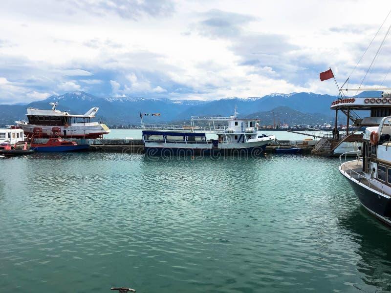 Много кораблей, шлюпки, вкладыши круиза в порте и вода на тропическом курорте лета моря против голубого неба и высоких гор стоковые изображения rf