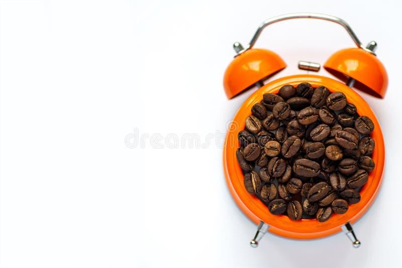 Много кофейных зерен в оранжевом будильнике на белой предпосылке стоковое изображение