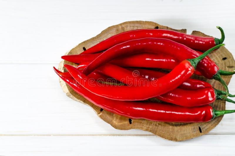 Много красные чили pepers лежат на овальной доске Брауна, которая стоит на белой деревянной таблице стоковые фото