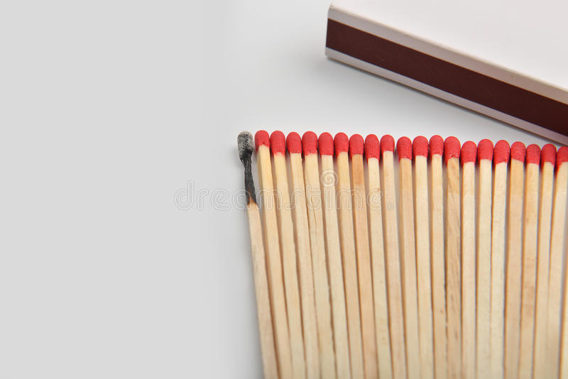 Много красных головных спичек и сгорели одно, который положенными прямо в линию около a стоковые изображения