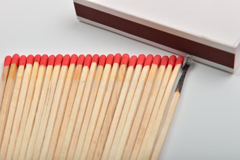 Много красных головных спичек и сгорели одно, который положенными прямо в линию около a стоковая фотография rf