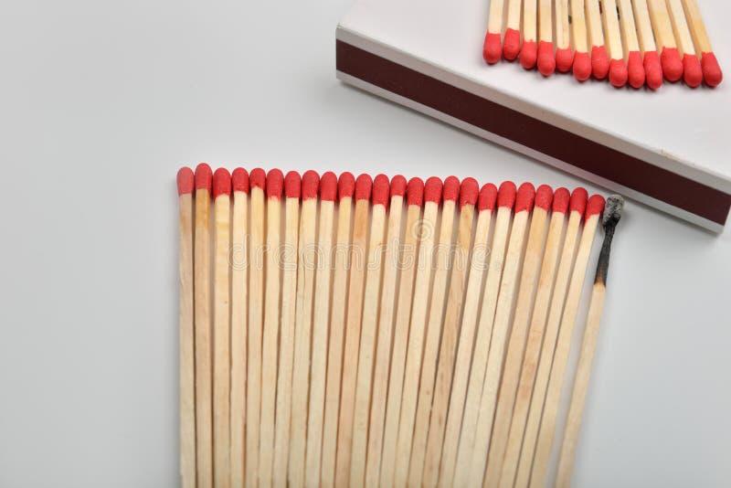 Много красных головных спичек и сгорели одно, который положенными прямо в линию около a стоковое фото rf