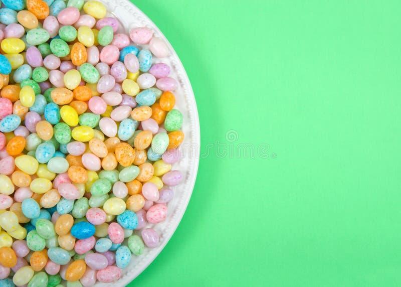 Много красочных желейных бобов конфеты на плите фарфора кладя на салатовую поверхность стоковое изображение