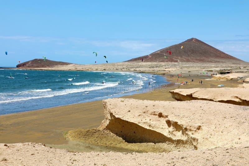 Много красочных змеев на серферах пляжа и змея ехать волны и летание во время ветреного дня в канарце El Medano в Тенерифе с стоковые фотографии rf