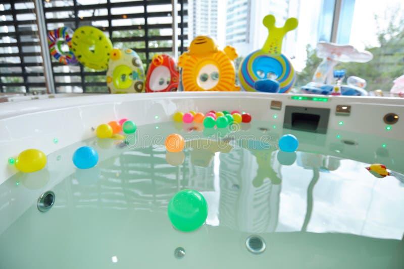 Много красочных раздувных шариков на воде и много резиновых колец конструируют для игры ребенк стоковые изображения rf