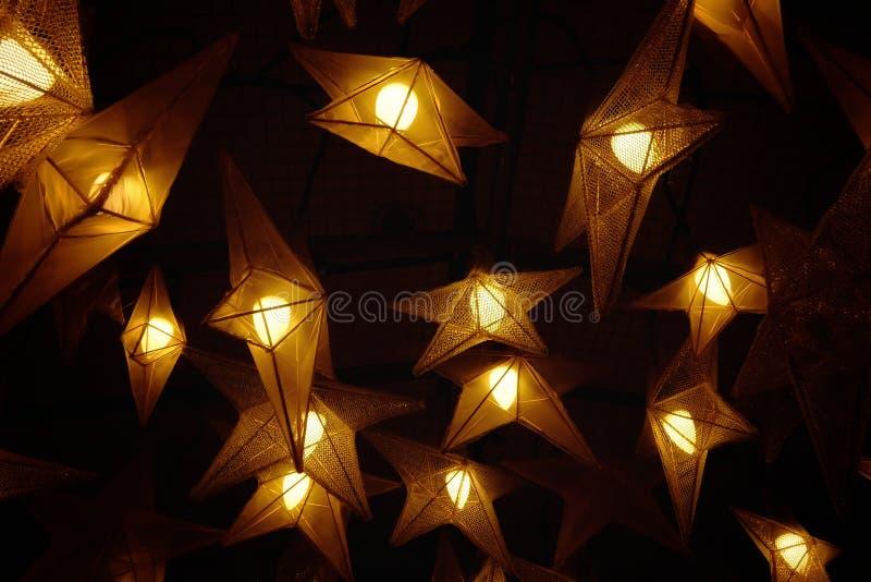 Много ламп звезды вися от потолка и накаляя в темной ночи стоковое изображение rf