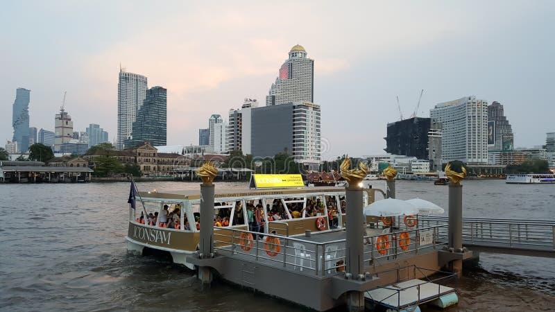 Много людей идут вниз от туристического судна для того чтобы прийти к торговому центру, значку Сиама, в вечере счастливо стоковые изображения rf