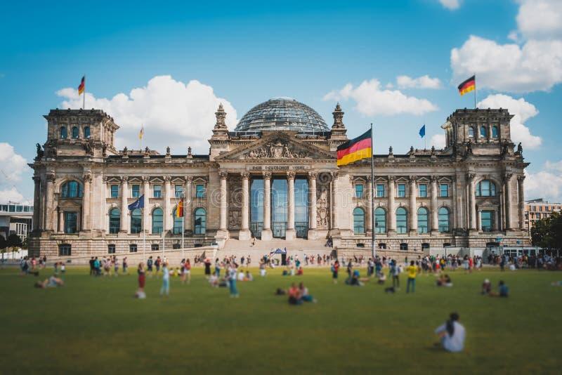 Много людей на луге перед зданием немецким Германским Бундестагом Reichstag, известным ориентиром на солнечном, летним днем стоковая фотография rf
