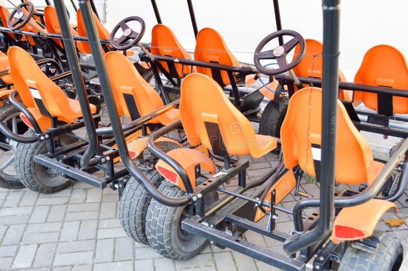 Много модных оранжевых четырехколесных велосипедов спорт, карты цикла для воссоздания спорт семьи и туризм с колесом и педалями стоковое фото rf
