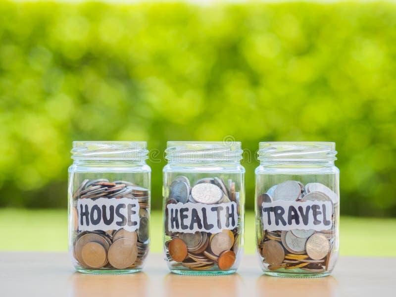 Много монетки в стеклянных деньгах раздражают на деревянной таблице Сбережения для дома стоковое изображение rf