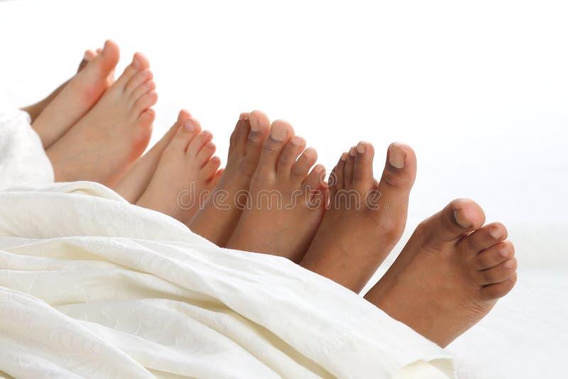 Много ног ` s детей peeking из-под одеяла стоковые изображения rf