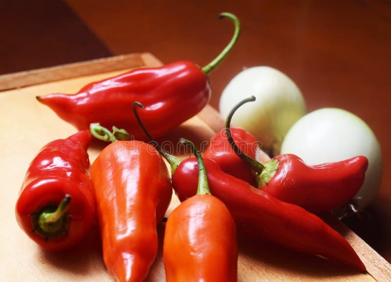Много перцев красного chili с луками стоковое изображение