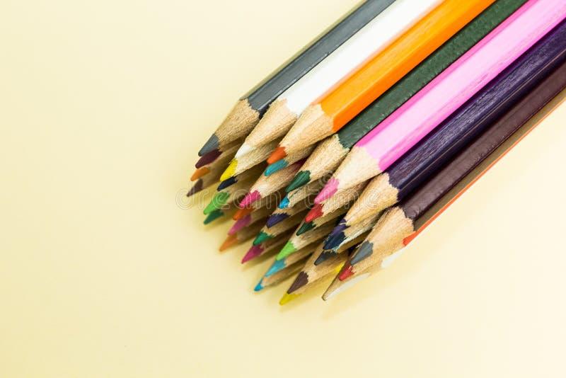 Много пестротканые карандаши на бежевой предпосылке стоковое изображение rf