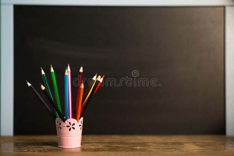 Много пестротканых карандашей в стекле на деревянном столе с черной предпосылкой задняя школа принципиальной схемы к стоковая фотография rf