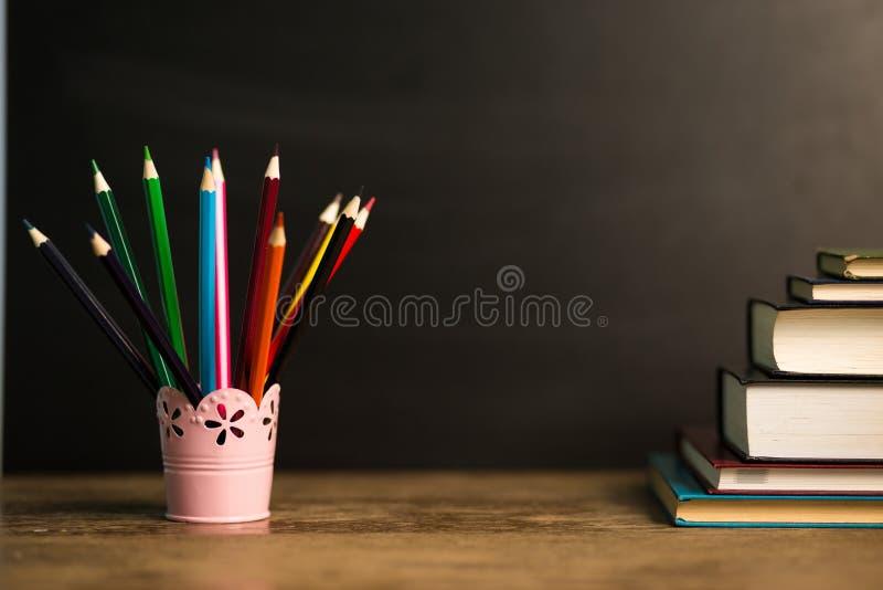 Много пестротканых карандашей в стекле на деревянном столе с черной предпосылкой задняя школа принципиальной схемы к стоковые изображения