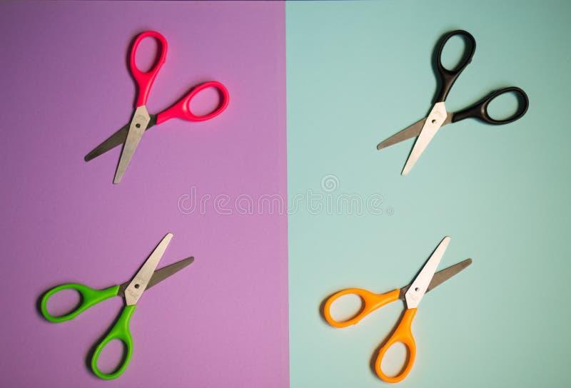 Много пестротканых ножниц на фиолетовой и голубой предпосылке стоковое фото rf