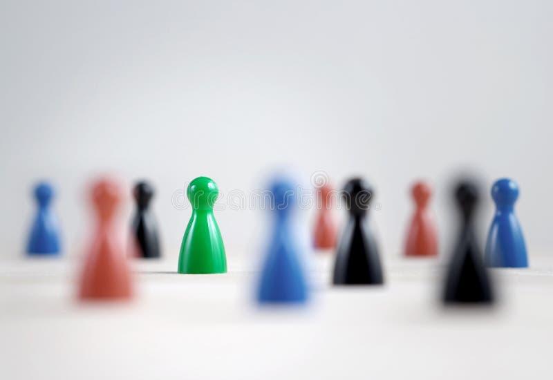 Много пешек настольной игры на таблице, селективном фокусе на зеленое одном стоковое изображение rf