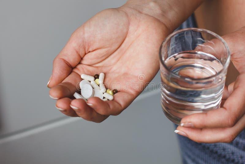 Много пилюльки и лекарств в руке женщины Она держит стекло воды Доктор посоветовал пилюлькам стоковое фото rf