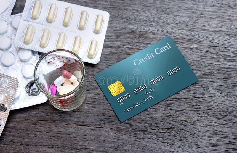 Много пилюлек или медицина и кредитная карточка на деревянной таблице Медицинский co стоковая фотография