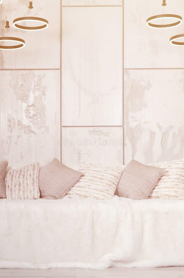 Много подушек лежат на кресле, которое покрыто с большой вуалью плюша на фоне мраморной стены стоковое изображение rf