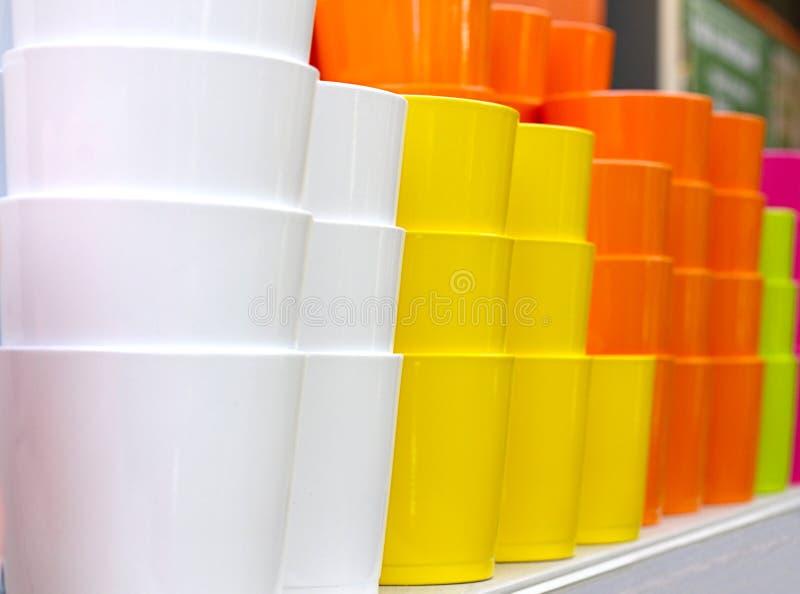 Много покрашенных керамических цветочных горшков штабелированы на полке в магазине оборудования сада Глина желтых, белых, апельси стоковые фотографии rf