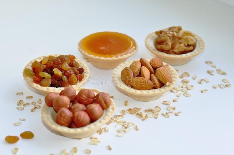 Много различных гаек полили в tartlets с медом стоковые фото