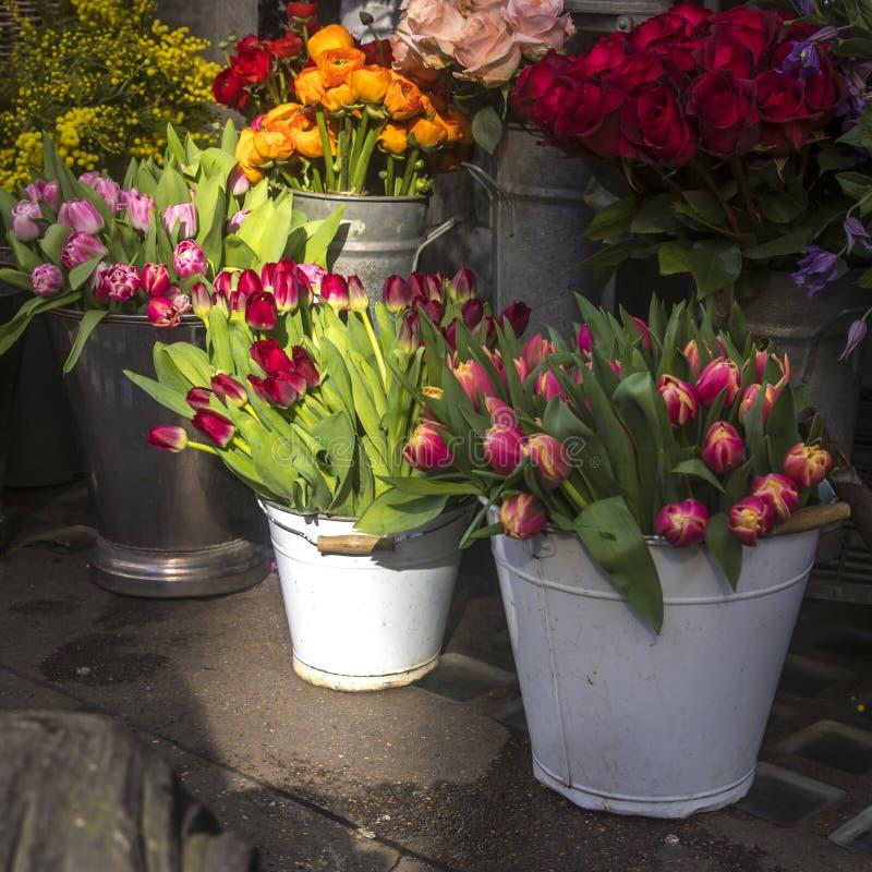 Много различных цветков весны в корзинах для букетов на продаже в рынке стоковая фотография