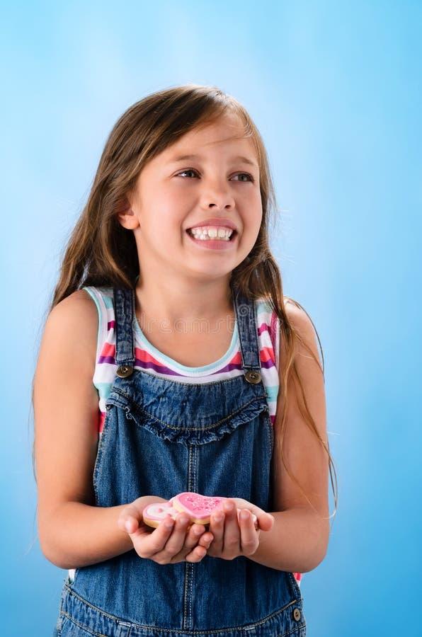 Много розовых печений формы сердца в руках маленькой девочки стоковые изображения rf