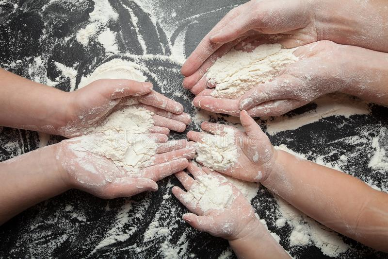 Много рук с пригорошнями муки, семьи варя тесто, хлеба и праздничных печений стоковое изображение rf