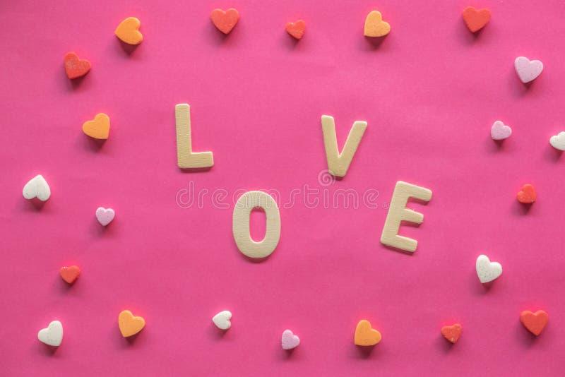 много сердец со словом ЛЮБОВЬЮ на розовой предпосылке, значке любов, дне Валентайн, концепции отношений стоковое изображение rf