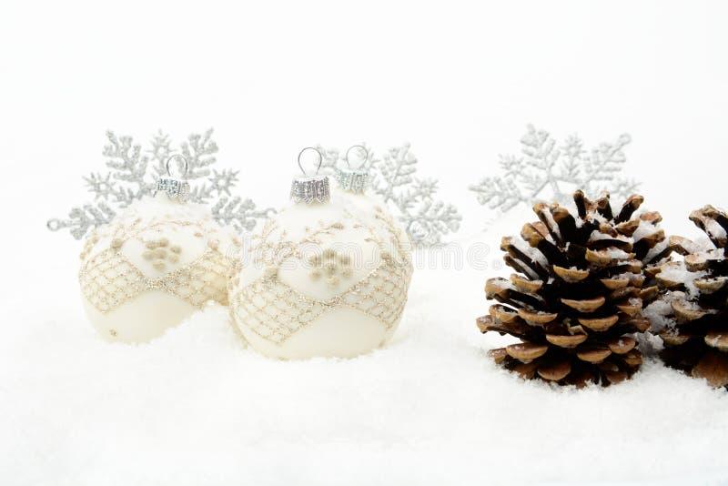 Много серебрят безделушки рождества, конусы сосны, снежинки на снеге стоковые фото