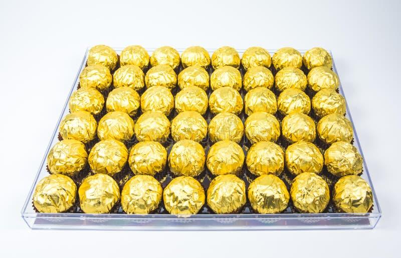 Много сияющая золотая оболочка шоколада в линии на белой предпосылке стоковые фото