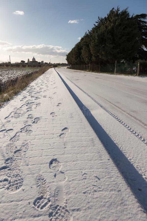 Много следов ноги на тротуаре покрытом снегом около длинного пути, стоковые изображения rf