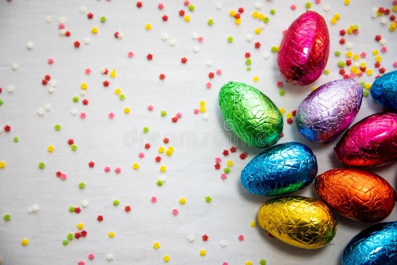 Много стоящих покрашенных пасхальных яя шоколада на белой предпосылке и красочном confetti стоковое фото rf