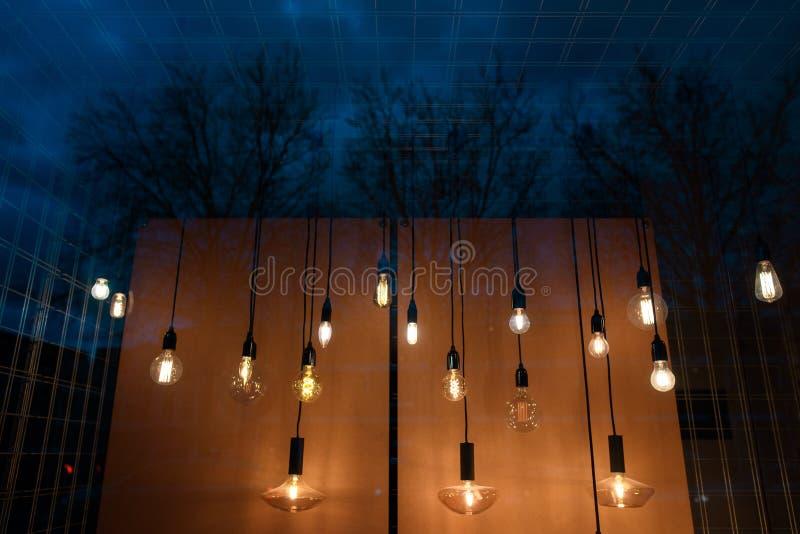 Много творческих ламп освещают окно на ноче стоковое изображение rf