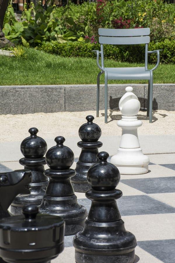 Много черных chessmen и белого епископа на доске улицы с стулом стоковое фото