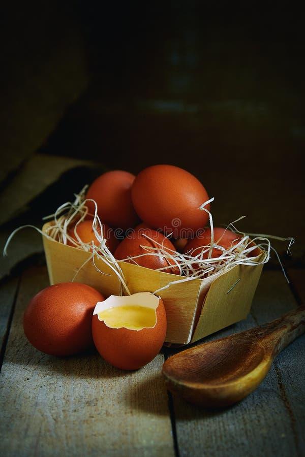 Много яя деревни лежат в плетеной корзине в курятнике на деревянном поле стоковое фото rf